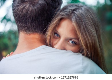 girl with beautiful blue eyes hugs boy. Happy lovers. woman with long hair looks out from behind man's shoulder. weak woman trusts man. Valentine's Day.
