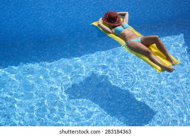 Girl with a beautiful body is relaxing on an air mattress in a pool