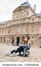 A girl in a beautiful coat stands near the Louvre.