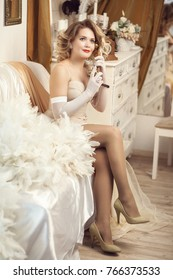 a girl in a beautiful dress and a feather boa speaks on an old telephone. Vertical shot. Style of the 20's, 30's