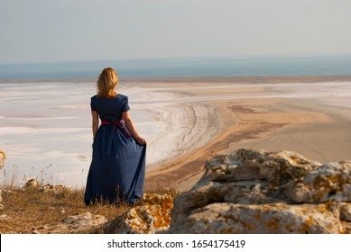 A girl in a beautiful dress looks into the distance. A girl in a long, blue dress stands on a mountain.