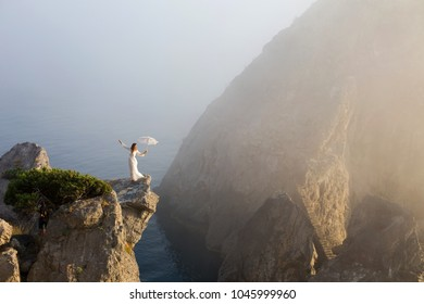 Girl in a beautiful dress on a cliff with an umbrella on sea background