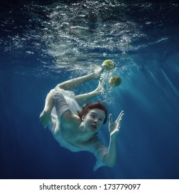 The girl in a beautiful dress under water and lemon.
