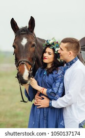 The girl in a beautiful dress and with a wreath on head holds a horse for a bridle and her boyfriend hugs her behind the waist and they look at the horse together