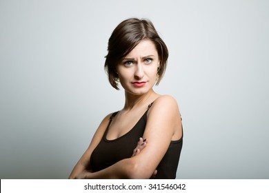 girl with a beautiful face offended, photo studio on isolated gray background