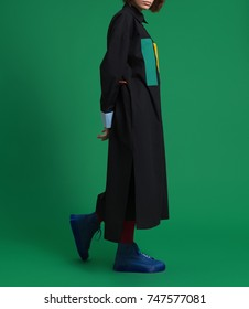 The girl in a beautiful, fashionable, luxurious black shirt, dress, robe, with yellow and green pockets, with different sleeves, and in blue shoes on a green background