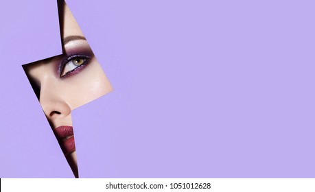 A girl with beautiful green bright eyes with blue shadows and bright purple lips looks into the hole of the colored paper.Fashion, beauty, make-up, cosmetics, beauty salon, style, personal care.