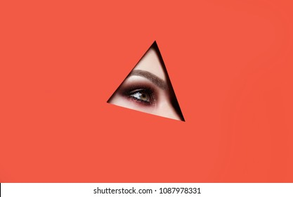 A girl with beautiful green bright eyes with brown shadows and expressive eyebrows looks into the hole of colored paper.