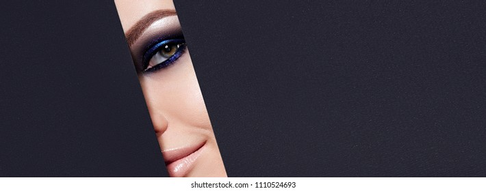 A girl with beautiful green bright eyes with blue shining shadows, beige lipstick and expressive eyebrows looks into the hole of colored paper.Fashion, beauty, make-up, cosmetics, beauty salon, style.