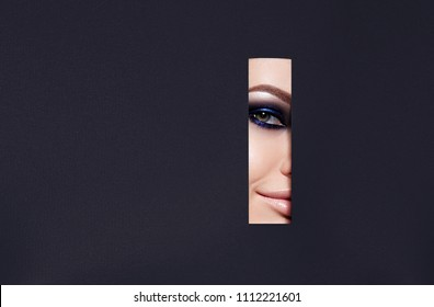 A girl with beautiful green bright eyes with blue shining shadows, beige lipstick and expressive eyebrows looks into the hole of colored paper.Fashion, beauty, make-up, color, sales, beauty salon, mak