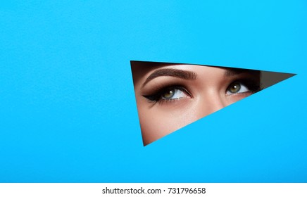 A girl with beautiful green bright eyes with brown shadows and expressive eyebrows looks into the hole of colored paper.Fashion, beauty, make-up, cosmetics, make-up artist, beauty salon,business card.