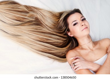 Girl with beautiful hair lying on the bed