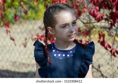 Girl with beautiful hair on a background of nature. Shy teenager in the sun. Schoolgirl on a background of nature. Schoolgirl on the background of autumn. Schoolgirl in a blue school dress. Schoolgirl