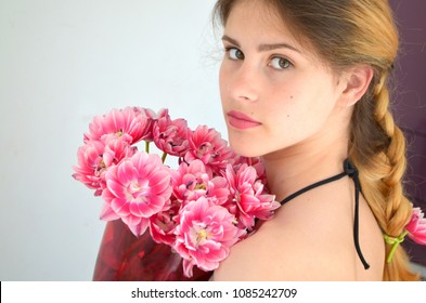 A girl with a beautiful hairdress with a bouquet of tulips is a sort of Columbus. Hair braided with four strands