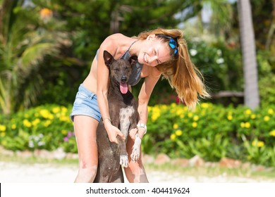 The girl beautiful in jeans shorts and an undershirt also gatsya with dogs, game with dogs on the beach