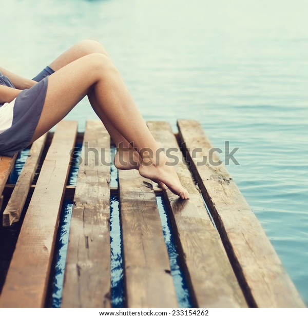 girl with beautiful legs sitting on the pier at the sea