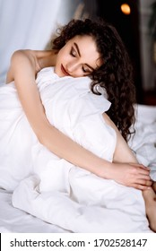 Girl in beautiful lingerie on the bed with white sheets and a blanket. Young woman resting at home in the morning