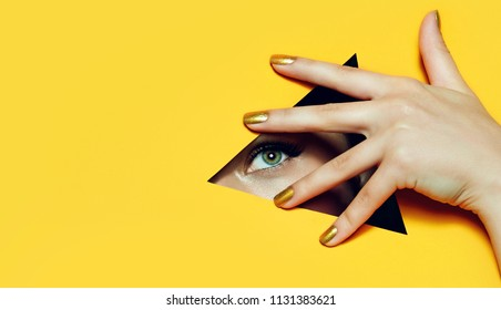A girl with beautiful long fingers and gold nail varnish covers her eyes in a triangular hole of orange paper.
