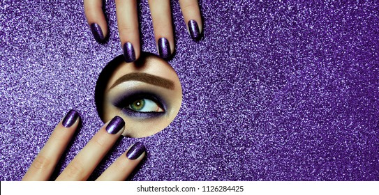 A girl with beautiful long fingers and lilac nails touches the edge of her open eye in a round hole of lilac shiny paper. A lilac eye shadow.