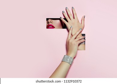 A girl with beautiful long fingers and silver nail polish with pink lipstick on the lips with metallic effect closes her eyes in a rectangular hole of pink paper of paper.