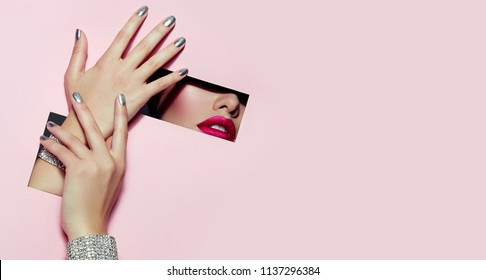 A girl with beautiful long fingers and silver nail polish with pink lipstick on the lips with metallic effect closes her eyes in a rectangular hole of pink paper of paper. Fashion, beauty, make-up.