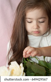 Girl with beautiful long hair stroking a bouquet of white roses