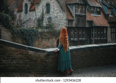 Girl with beautiful long hair in vintage dress standing at the bridge in the morning