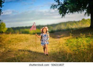 girl in the beautiful park, with a net catches butterflies, smiles and laughs, playful mood, childish pranks
