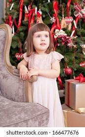Girl in a beautiful pink dress stands near a Christmas fir-tree