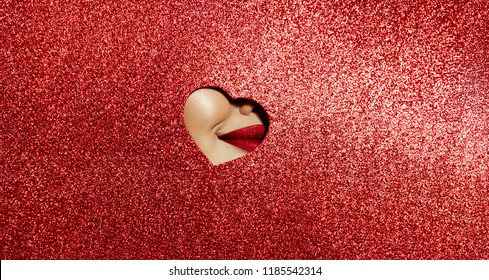 A girl with beautiful plump lips, painted pink lipstick with a metallic effect. Lips in a hole in the form of a heart of pink shiny paper.Fashion, beauty, make-up, cosmetics, beauty salon, style.