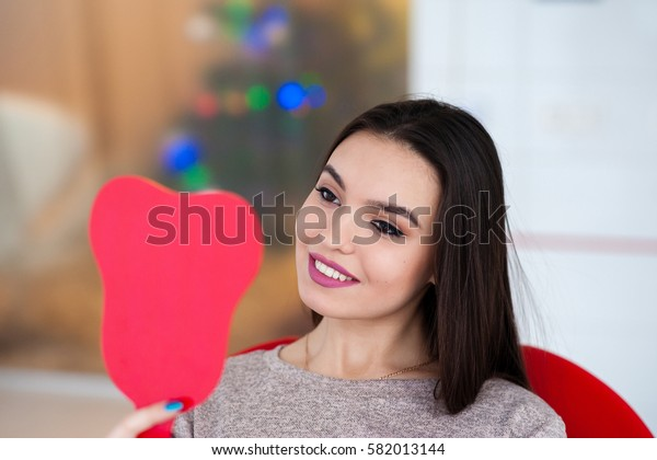 The girl with a beautiful smile looks in the mirror.
