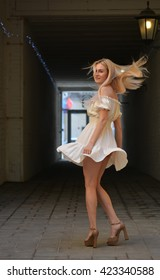 Girl in beautiful summer fashion dress goes through underpass