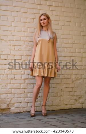 219b8a0af2b Girl in beautiful summer fashion dress stands near a yellow brick wall