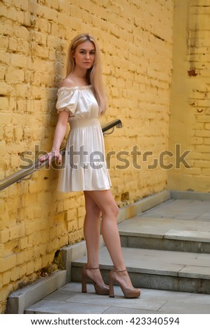 219b8a0af2b Girl in beautiful summer fashion dress stands near a yellow brick wall