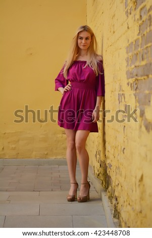 8415f4bb860 Girl in beautiful summer fashion purple red dress stands near a yellow  brick wall