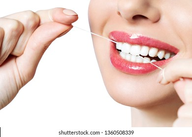 A girl with beautiful white teeth, charmingly smiling. A young woman caring for the mouth, performs cleaning of the teeth, dental floss.. Dental health background