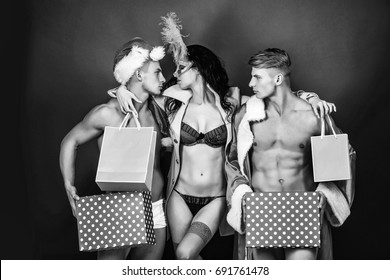 girl or beautiful woman in mask with feathers and men in santa suits with Christmas presents, black and white