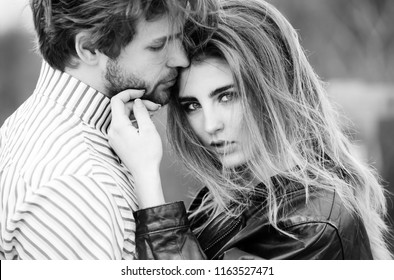 girl or beautiful woman with stylish, long hair and fashion makeup touching face of handsome, bearded man with beard. Young couple of lovers on natural background. Love and tenderness