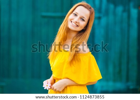 A girl in a beautiful yellow dress holds a flower in her hand against the  background e536ea2a8