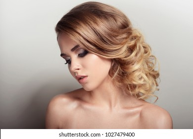 girl beauty portrait with make-up blond curls hair style photo on gray white background blue eyes cute appearance beautiful make-up artist green shadows red lips sparkles sad serious