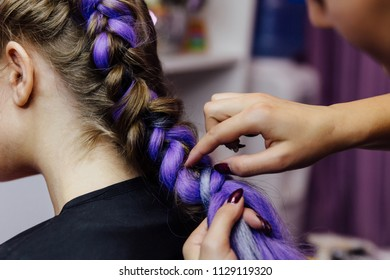 girl in the beauty salon hairdresser is weaved with braids. braided pigtails. Braiding with synthetic purple color kanekalon Close-up.