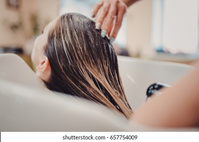 girl in a beauty salon. wash your hair, hair care, health. Process of washing your hair in a hairdresser. The hands of the hairdresser wash the client's head