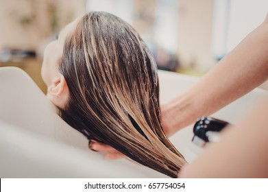 girl in a beauty salon. wash your hair, hair care, health. Process of washing your hair in a hairdresser
