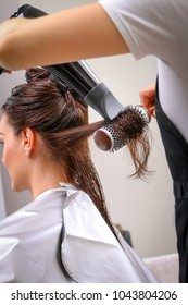 Girl in beauty salon while an hair stylist dry her hair