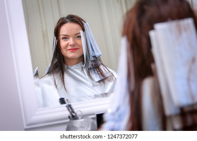 Girl in beauty salon while an hair stylist dyeing her hair