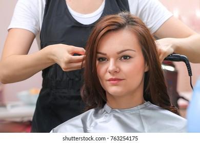 Girl in beauty salon while an hair stylist dry her hair