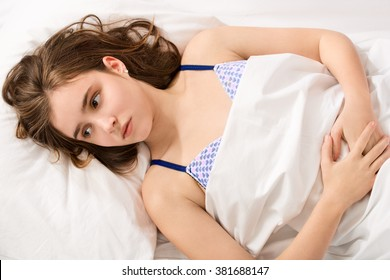 girl became a woman concept - young girl lying with period pain