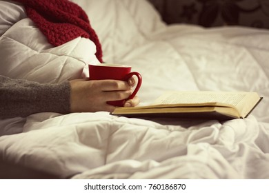 Girl in bed with a book and a cup of hot tea.
