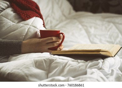 Girl in bed with a book and a cup of tea.
