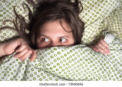 Girl in bed at home hiding under the blanket